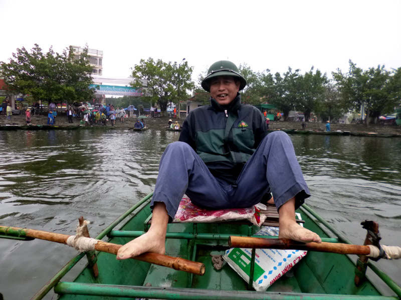 Our tour guide rowing down the river using his feet in Ninh Binh, Vietnam