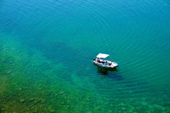 A boat in Lake Ohrid in clear turquoise water, North Macedonia